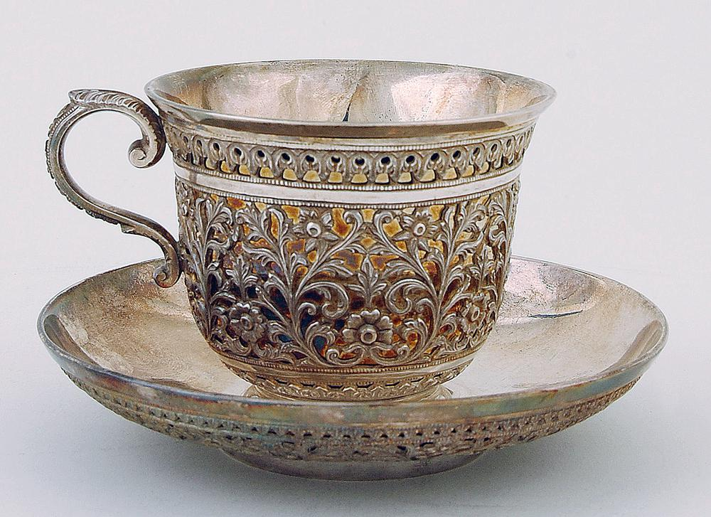 Tea-cup and saucer.  Each element is made up of an outer and an inner skin of silver; the decoration appears on the outer skin while the inner face is undecorated and shiny.  The decorated part appears as a pierced skin through which the shiny interior part can be seen.  These separate parts are screwed together on the base.  The decoration on both cup and saucer is the same – a main band of floral scrollwork with, above and below, a small band of acanthus leaves.