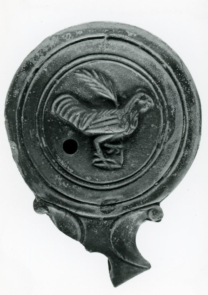 Mould-made pottery lamp with a voluted angular-tipped nozzle (broken), a flat shoulder and a broad inward-sloping moulded rim. The discus is decorated with a cock holding a palm-branch. Within the slightly raised base is a faint mould-mark in the form of