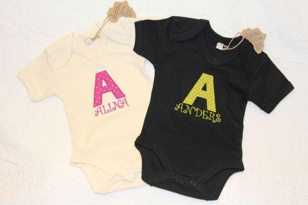 Baby body med en applikation och namn broderat på bröstet.