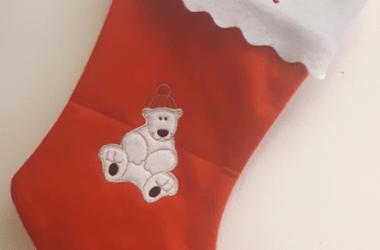 Julstrumpa med olika julmotiv i applikation och namn broderat.