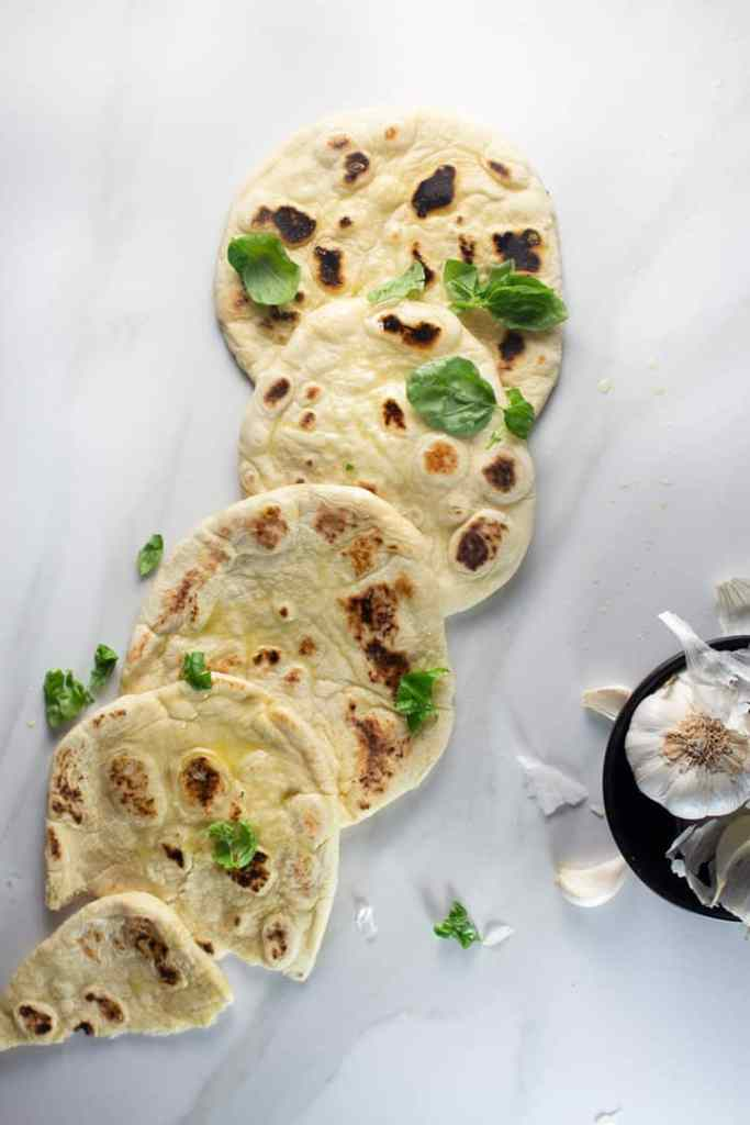Vegan Naan Bread with a drizzle of olive oil and basil