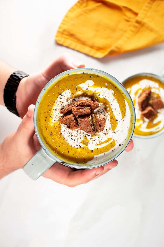 Creamy Red Lentil Soup garnished with croutons and coconut cream
