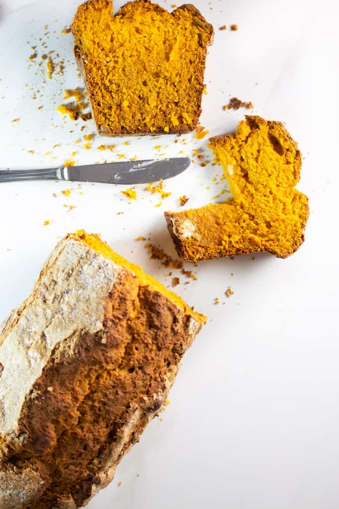 sliced pumpkin bread on a white marble surface