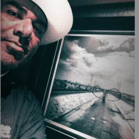 George Lopez posing with one of Art Meza's iconic photos from Lowriting.