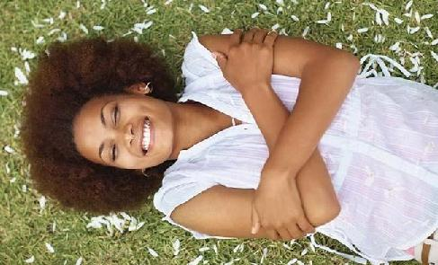woman laying on grass smiling