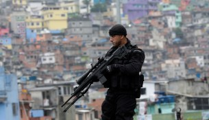 "A sniper holds his gun in front of Rocinha slum during the inauguration of its Peacekeeping Unit Program (UPP) in Rio de Janeiro September 20, 2012. The occupation of Rocinha, a notorious hillside ""favela"" that overlooks some of Rio's swankiest areas, is a crucial part of the city's preparations to host soccer's World Cup in 2014 and the Olympics two years later. REUTERS/Ricardo Moraes (BRAZIL - Tags: CIVIL UNREST CRIME LAW) - RTR38739"