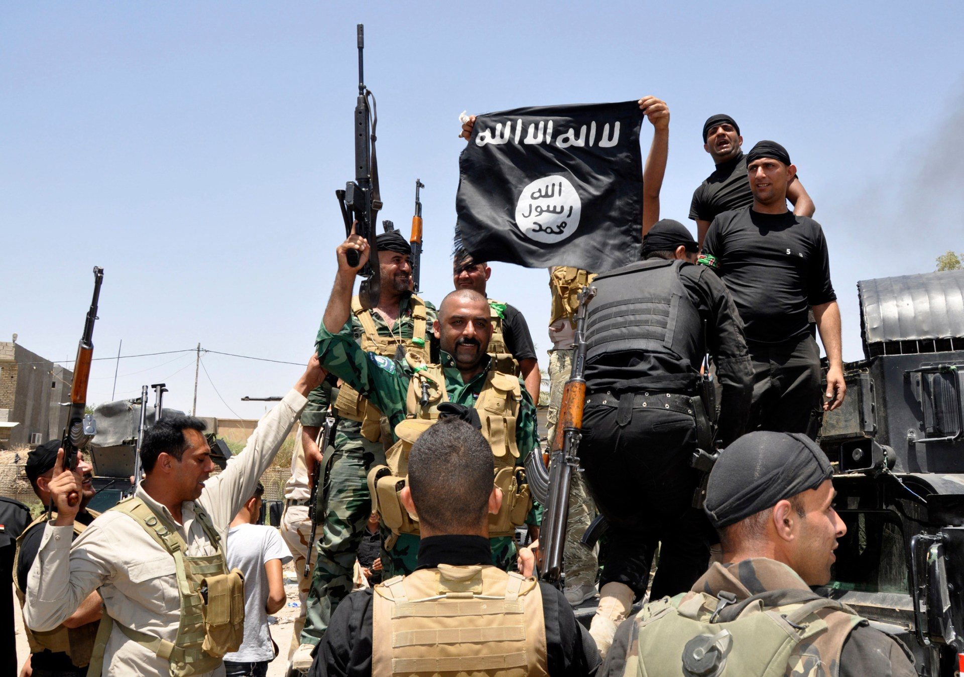 Reuters - Iraqi security forces pull down a flag belonging to Sunni militant group Islamic State of Iraq and the Levant (ISIL) during a patrol in the town of Dalli Abbas in Diyala province, June 30, 2014.