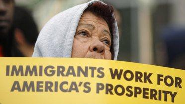 "Woman holding sign reading ""Immigrants work for America's prosperity"""