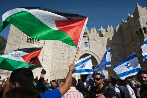 Palestinian and Israeli flags being waved.