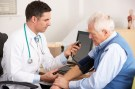 An elderly man gets his blood pressure taken