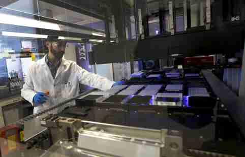 Technician Matthew Smith loads a robotic DNA sample automation machine