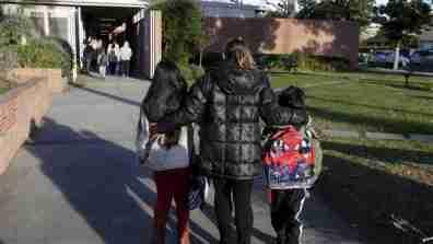 A mother escorts her children to elementary school.