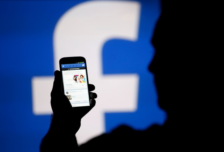 A man is silhouetted against a video screen with an Facebook logo as he poses with an Samsung S4 smartphone in this photo illustration taken in the central Bosnian town of Zenica, August 14, 2013. REUTERS/Dado Ruvic/File Photo - RTX2IVBO