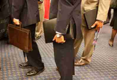 Attendees carry their resumes at a job fair