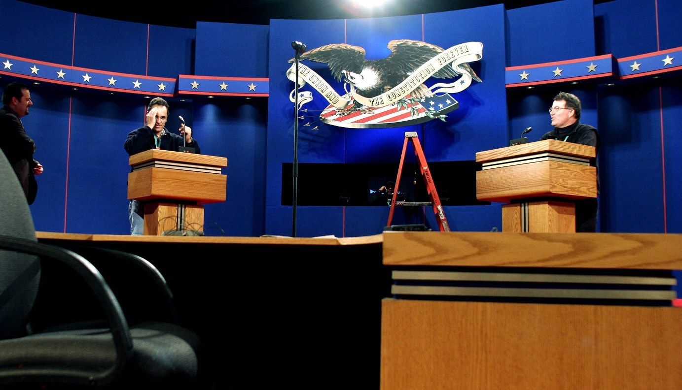 Two production staff stand at the debate podiums while the stage is being prepped. A ladder stands in the background.