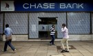 People walk past a Chase Bank branch, now managed by Kenya Commercial Bank (KCB), after its reopening in downtown Nairobi, Kenya April 27, 2016. REUTERS/Thomas Mukoya - RTX2BUEP