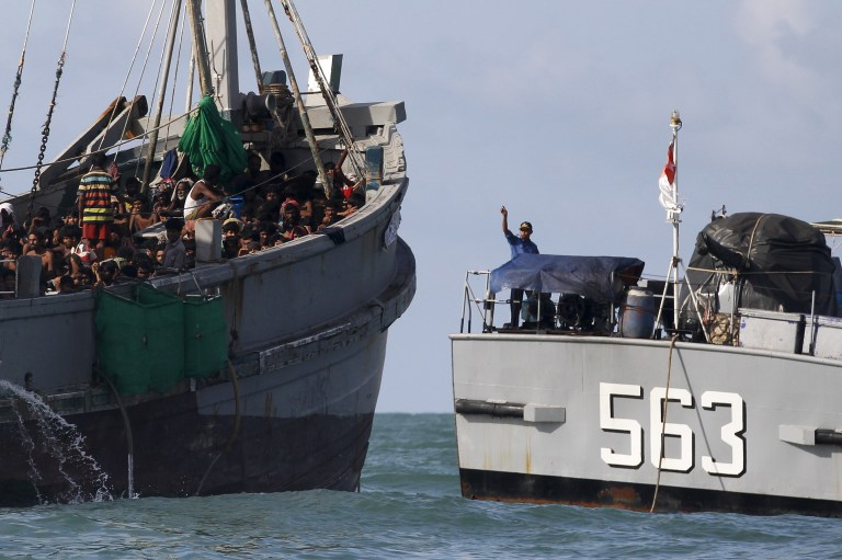 A Myanmar military officer (R) gestures from a navy ship towards a boat packed with migrants, off Leik Island in the Andaman Sea May 31, 2015. More than 700 migrants found packed aboard an overcrowded boat in the Andaman Sea were still being held offshore by Myanmar's navy on Monday, more than three days after the converted fishing vessel was intercepted off the country's coast. Picture taken May 31, 2015. REUTERS/Soe Zeya Tun - RTR4YF8E