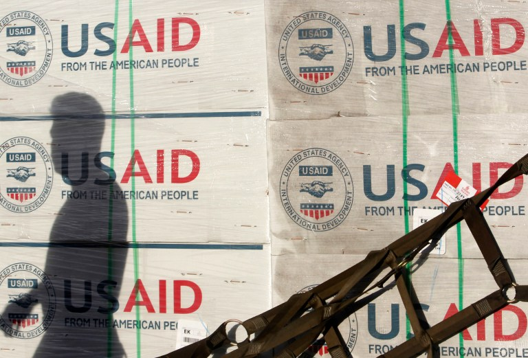 The shadow of a Philippine Army personnel is cast on boxes of relief items from U.S. Agency for International Development (USAID) for the victims of super typhoon Haiyan, at Villamor Air Base in Manila November 13, 2013. The Philippine government has been overwhelmed by the force of the typhoon, which decimated large swathes of Leyte province where local officials have said they feared 10,000 people died, many drowning in a tsunami-like surge of seawater. REUTERS/Cheryl Ravelo (PHILIPPINES - Tags: DISASTER ENVIRONMENT) - RTX15BB2