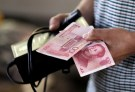 A customer holds a 100 Yuan note at a market in Beijing, August 12, 2015.  REUTERS/Jason Lee/File Photo   - RTSP2II