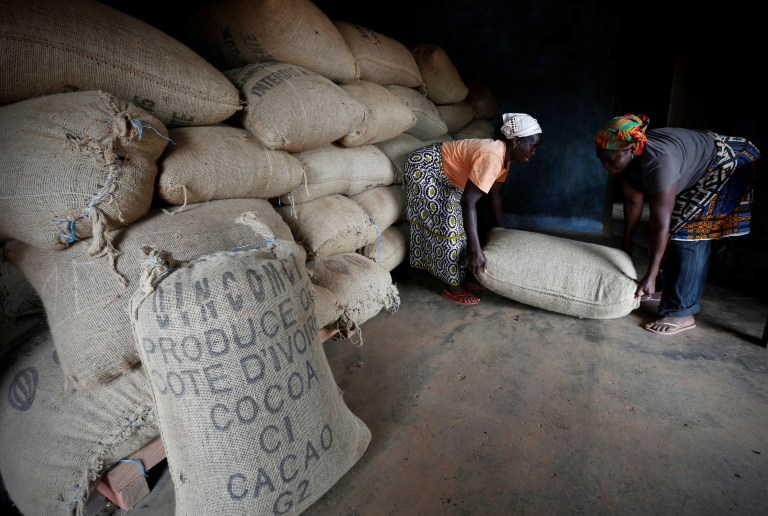 Women from a local cocoa farmers association lift a sack in a cocoa warehouse in Djangobo, Ivory Coast, November 17, 2014. REUTERS/Thierry Gouegnon/File Photo - RTSRWG9