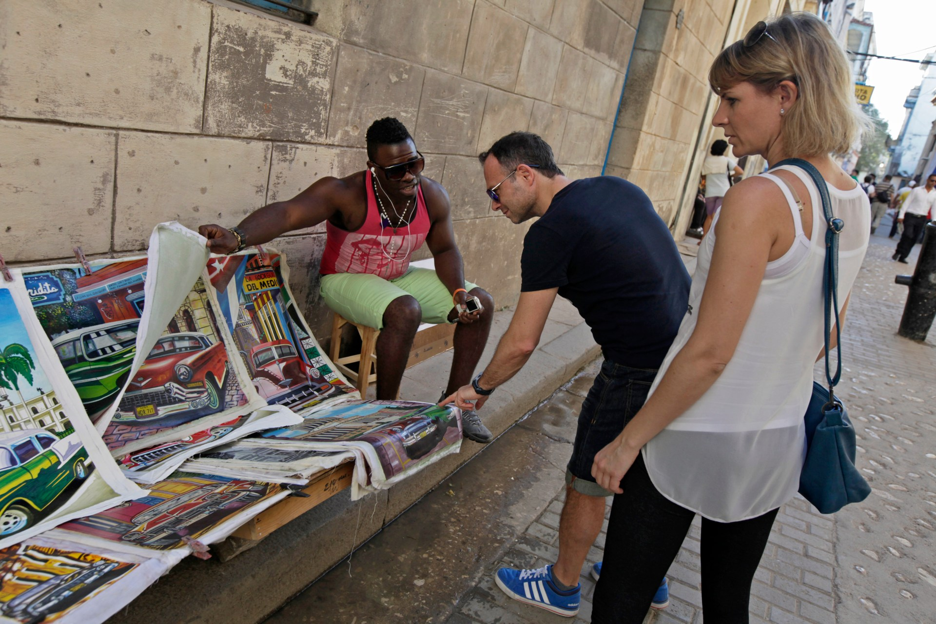 A man shows tourists prints for sale in Old Havana December 18, 2014. From bus drivers to bartenders and ballet dancers, many Cubans are already imagining a more prosperous future after the United States said it will put an end to 50 years of conflict with the communist-run island. News of the historic shift echoed quickly through the Spanish colonial plazas of Old Havana, where strains of trova and son rose from outdoor cafes, Cuban music that is a siren song for foreign tourists. REUTERS/Enrique De La Osa (CUBA - Tags: POLITICS SOCIETY TRAVEL) - RTR4IMCL