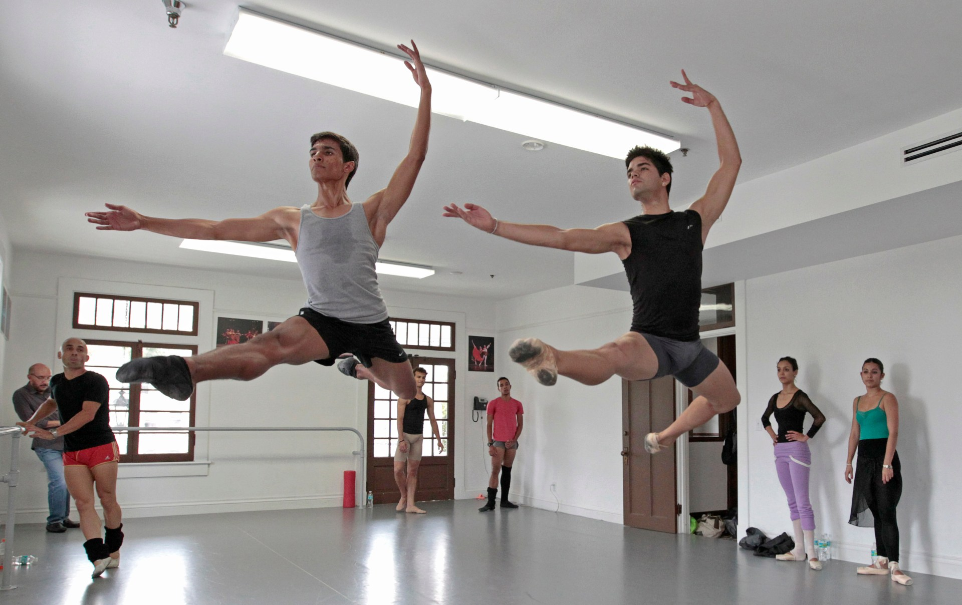 Dancers Josue Justiz (L) and Edward Gonzalez Morgado from the Cuban National Ballet, who defected last month, leap during their audition at the Miami Hispanic Ballet in Miami, Florida April 4, 2013. The Cuban national ballet, known for its adherence to a classical style of ballet and for producing many world-class dancers, regularly makes international tours. Over the years, many of its dancers have defected and joined other companies abroad. Others have been allowed to leave Cuba freely, including Carlos Acosta with the Royal Ballet in London and Jose Manuel Carreno, who retired in 2011 as a much revered principal dancer at the American Ballet Theatre in New York. REUTERS/Joe Skipper (UNITED STATES - Tags: POLITICS SOCIETY IMMIGRATION) - RTXY8T3