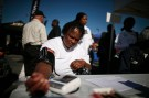 Bernita Jackson, 51, has her blood pressure measured at an event to inform people about the Affordable Care Act and donate turkeys to 5,000 needy families, in Los Angeles, California, November 25, 2013.  REUTERS/Lucy Nicholson (UNITED STATES - Tags: HEALTH SOCIETY POVERTY POLITICS) - RTX15SZ8