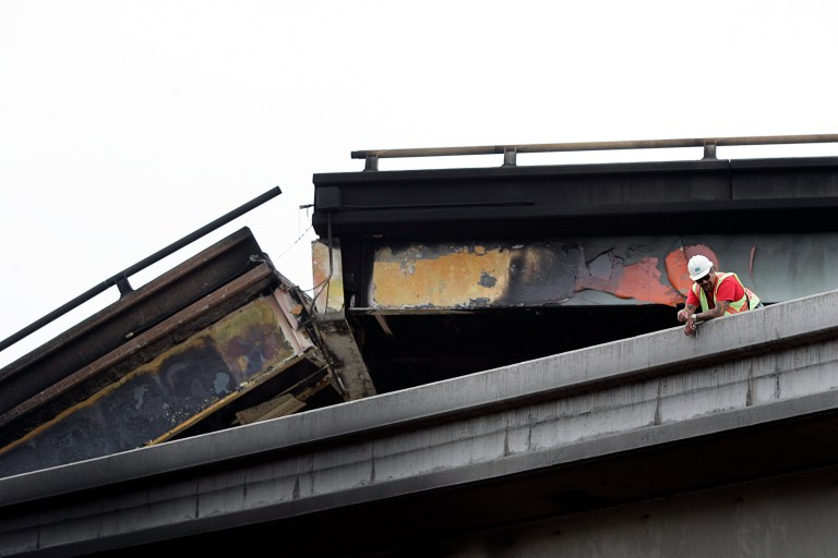 A city employee inspects a collapsed highway in Oakland, California