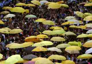 """Pro-democracy protesters carrying yellow umbrellas, symbol of the Occupy Central civil disobedience movement, gather outside government headquarters in Hong Kong, China September 28, 2015. Monday marks the first anniversary of the Occupy Central or """"umbrella"""" movement, demanding universal suffrage in the territory. REUTERS/Bobby Yip - RTX1SU40"""