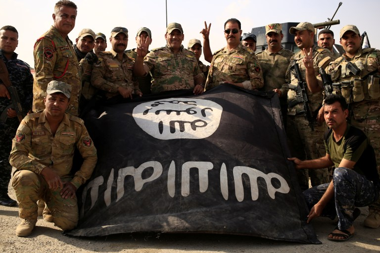 Iraqi soldiers celebrate as they pose with the Islamic State flag along a street of the town of al-Shura, which was recaptured from Islamic State (IS) on Saturday, south of Mosul, Iraq October 30, 2016. REUTERS/Zohra Bensemra - RTX2R34S