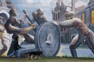 A man walks his dog past a mural depicting factory workers in Chicago.