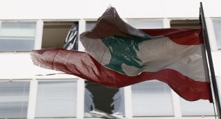 "Lebanon's flag flies in front of damaged windows at the Starco building in front of the site of a bomb blast, which killed Lebanon's former Finance Minister Mohamad Chatah, in downtown Beirut December 28, 2013. Chatah, who opposed Syrian President Bashar al-Assad, was killed in a massive bomb blast on Friday which one of his political allies blamed on the Shi'ite Hezbollah militia. Former prime minister Saad al-Hariri accused Hezbollah of involvement in the killing of Chatah, his 62-year-old political adviser, saying it was ""a new message of terrorism"". REUTERS/Jamal Saidi (LEBANON - Tags: CIVIL UNREST POLITICS) - RTX16VMI"