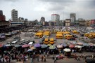 People walk past roadside stalls with umbrellas in the central business district, near Marina in Lagos, Nigeria December 13, 2016.REUTERS/Akintunde Akinleye - RTX2UUPF