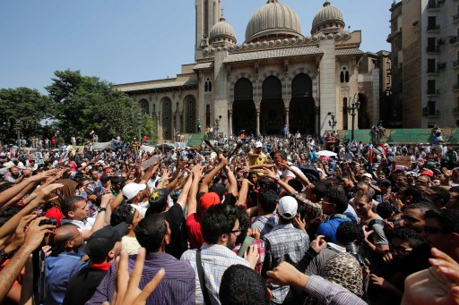 """Supporters of deposed Egyptian President Mohamed Mursi shout slogans during a protest outside Al-Fath Mosque in Ramses Square, in Cairo August 16, 2013. Thousands of supporters of Mursi took to the streets on Friday, urging a """"Day of Rage"""" to denounce this week's assault by security forces on Muslim Brotherhood protesters that killed hundreds. The army deployed dozens of armored vehicles on major roads in Cairo, and the Interior Ministry has said police will use live ammunition against anyone threatening state installations. REUTERS/Youssef Boudlal (EGYPT - Tags: POLITICS CIVIL UNREST) - RTX12NNE"""