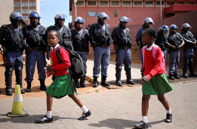 School girls walk past riot police standing guard outside Hillbrow magistrate court during an appearance of students who were arrested during a protest demanding free education at the Johannesburg's University of the Witwatersrand