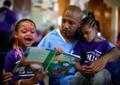 """Donte (R), 34, who said he has one year left in prison, reads a book with his daughters Cieara (L), 7, and Nicole, 3, at San Quentin state prison for a Father's Day visit organised by """"Get on the Bus"""" in San Quentin California, June 8, 2012. An annual Fathers' Day event, """"Get On The Bus"""" brings children in California to visit their fathers in prison. Sixty percent of parents in state prison report being held over 100 miles (161 km) from their children. Regular prison visits lower rates of recidivism for the parent, and make the child better emotionally adjusted and less likely to become delinquent, according to The Center for Restorative Justice Works, the non-profit organization that runs the """"Get on the Bus"""" program. Picture taken June 8, 2012.     REUTERS/Lucy Nicholson (UNITED STATES - Tags: CRIME LAW SOCIETY) - RTR33NJM"""