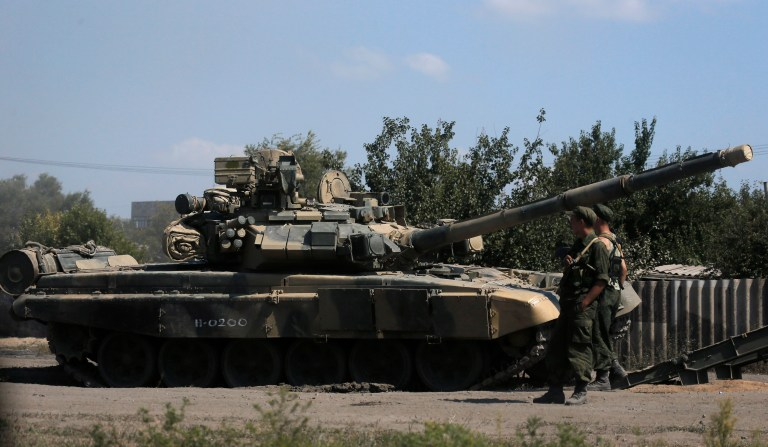 Russian soldiers are pictured next to a tank in Kamensk-Shakhtinsky, Rostov region, near the border with Ukraine, August 23, 2014. NATO Secretary General Anders Fogh Rasmussen said on Friday the alliance had observed an alarming build-up of Russian ground and air forces in the vicinity of Ukraine. REUTERS/Alexander Demianchuk (RUSSIA - Tags: MILITARY POLITICS CIVIL UNREST CONFLICT) - RTR43GHH