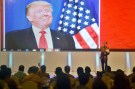 Indonesian President Joko Widodo speaks to local company executives as a picture of U.S. President-elect Donald Trump is shown on a screen behind him