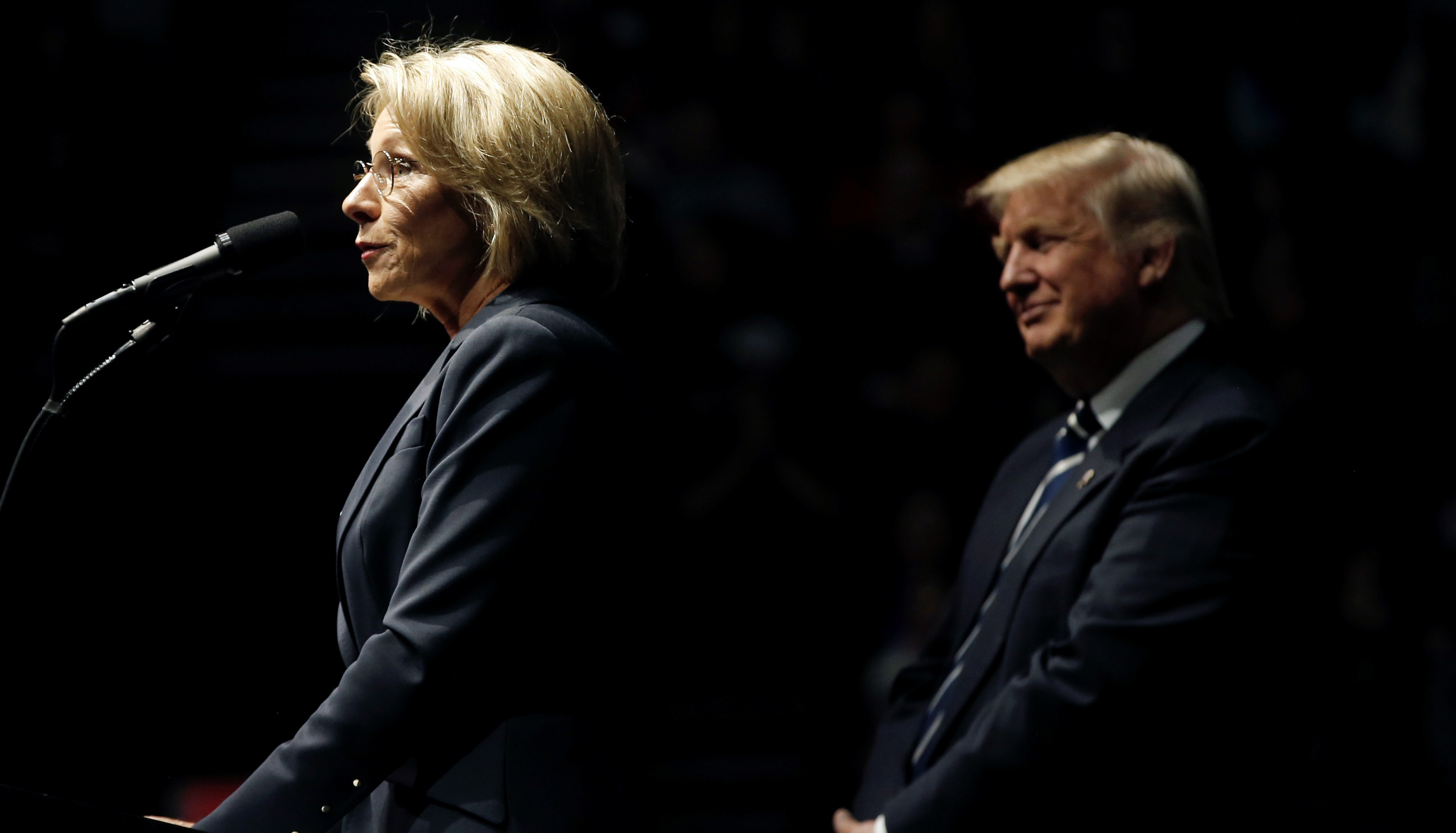 "U.S. President-elect Donald Trump looks on as his choice for U.S. Education Secretary Betsy DeVos speaks at a ""Thank You USA"" tour rally in Grand Rapids, Michigan, U.S. December 9, 2016."