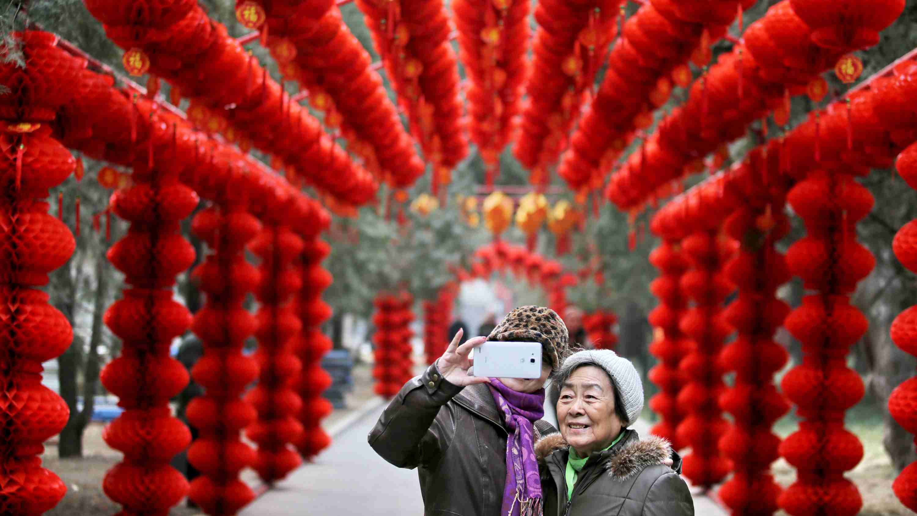 Visitors take a selfie in front of lantern decorations installed to prepare for Spring Festival celebrations in a temple fair at a park, in Beijing February 6, 2015. The Chinese Lunar New Year on Feb. 19 will welcome the Year of the Sheep (also known as the Year of the Goat or Ram). Picture taken February 6, 2015. REUTERS/Stringer (CHINA - Tags: ANNIVERSARY SOCIETY TPX IMAGES OF THE DAY) CHINA OUT. NO COMMERCIAL OR EDITORIAL SALES IN CHINA - RTR4OKYL