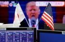 National flags of Japan and the U.S. are seen in front of a monitor showing U.S. President Donald Trump at a foreign exchange trading company in Tokyo, Japan, January 23, 2017.    REUTERS/Toru Hanai - RTSWVU7