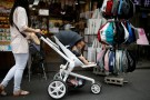 A woman pushing her baby in a stroller shops in the Hongdae area of Seoul, South Korea, June 29, 2016. Picture taken June 29, 2016. REUTERS/Kim Hong-Ji - RTX2J5I6
