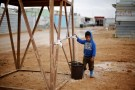 A Syrian refugee child collects water during rainy weather at the Al Zaatari refugee camp in the Jordanian city of Mafraq, near the border with Syria December 18, 2016. REUTERS/Muhammad Hamed