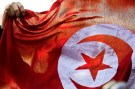 A person holds up a Tunisian flag and shouts slogans during celebrations marking the fourth anniversary of Tunisia's 2011 revolution, in Tunis