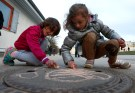 Children of migrants use chalk while playing in a refugee deportation registry centre in Manching near Ingolstadt, Germany, February 16, 2016. Picture taken on February 16, 2016.  REUTERS/Michaela Rehle - RTX27BY2