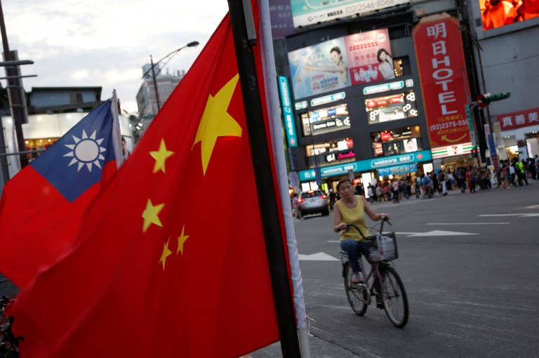 A woman rides a bike past Taiwan and China national flags during a rally held by a group of pro-China supporters calling peaceful reunification, 6 days before the inauguration ceremony