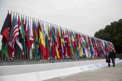 People walk in front of national flags which are set up for the upcoming 2nd World Internet Conference in Jiaxing
