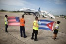 Ground crew hold U.S. and Cuban flags near a recently landed JetBlue aeroplane, the first commercial scheduled flight between the United States and Cuba in more than 50 years, at the Abel Santamaria International Airport in Santa Clara, Cuba, August 31, 2016. REUTERS/Alexandre Meneghini - RTX2NQET
