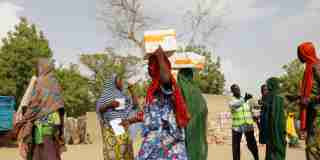 Women carry food supplement received from World Food Programme (WFP) at the Banki IDP camp, in Borno, Nigeria April 26, 2017. Picture taken April 26, 2017. REUTERS/Afolabi Sotunde - RTS14ZP0