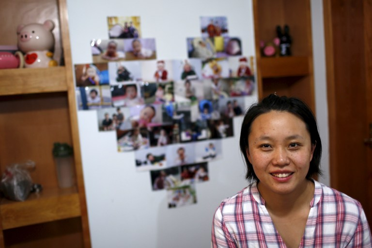 Zhang Yingyi, a 30-year-old administrative assistant and a mother of a three-year-old girl, smiles as she poses for a photograph at her home in Shanghai, China,